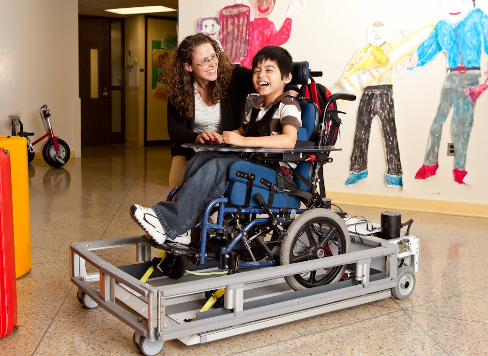 a woman kneels next to a child in a mobility aid